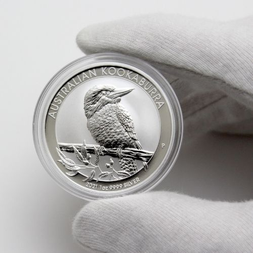 An Australian coin in its plastic case being held with cloth gloves